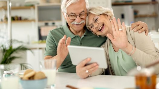 Happy,Senior,Couple,Using,Touchpad,And,Waving,While,Greeting,Someone